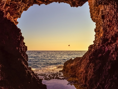 Sea caves - parachute against sunset